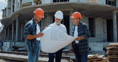 Photo for Engineer and builders in hard hats discussing blueprint on construction site - Royalty Free Image