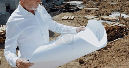 Cropped view of engineer holding blueprint on construction site