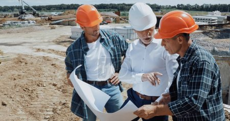 Photo for Engineer and builders discussing blueprint on construction site - Royalty Free Image