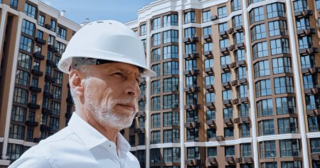 middle aged engineer looking away near building on background