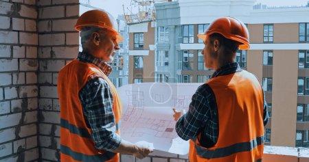 Photo pour Bâtisseurs en gilets de sécurité avec un plan parlant sur le chantier de construction - image libre de droit