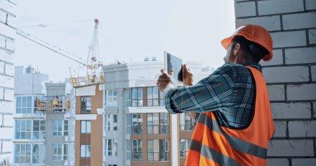 Photo pour Builder prendre des photos avec tablette numérique sur le chantier de construction - image libre de droit