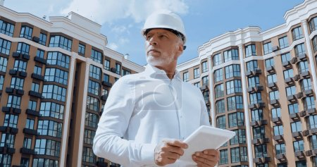 Photo for Low angle view of mature engineer using digital tablet with building on urban street at background - Royalty Free Image