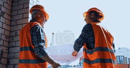 Photo pour Vue à faible angle des constructeurs dans les gilets de sécurité avec un plan parlant sur le chantier de construction - image libre de droit
