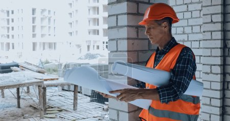 Pensive builder in helmet looking at blueprint on construction site