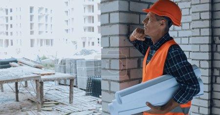 Photo pour Constructeur pensif dans le casque tenant des plans sur le chantier de construction - image libre de droit