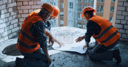 Photo for Three builders in hand hats discussing blueprint while sitting on construction site - Royalty Free Image