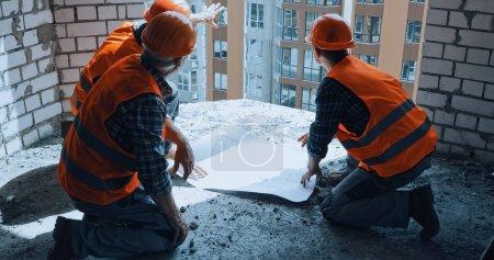 Photo pour Bâtisseurs chapeaux à la main discutant du plan tout en étant assis sur le chantier de construction - image libre de droit