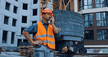 Photo pour Bâtisseur debout avec la main sur la hanche et en utilisant talkie walkie sur le chantier de construction - image libre de droit