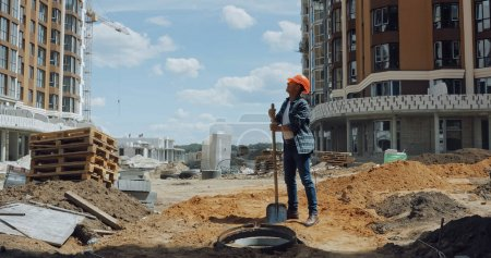 Photo for Middle aged builder in hard hat holding shovel on construction site - Royalty Free Image