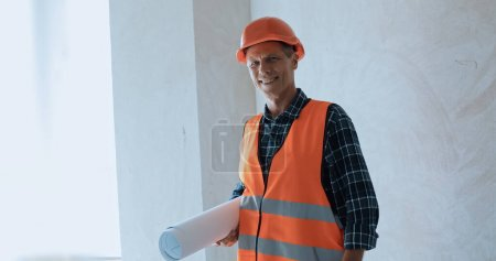 Smiling builder holding blueprint and looking at camera on construction site