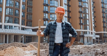 Photo for Smiling builder holding shovel and standing with hand on hip on construction site - Royalty Free Image