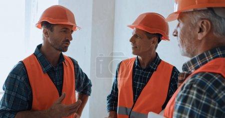 Photo pour Les constructeurs de casques de sécurité parlent sur le chantier de construction - image libre de droit