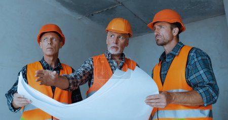 Builders in safety helmets talking near blueprints on construction site