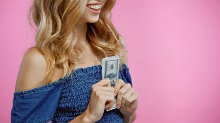 Photo for Cropped view of happy blonde woman holding dollars isolated on pink - Royalty Free Image