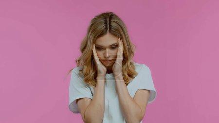 aufgebrachte Frau berührt Schläfen und blickt vereinzelt auf rosa