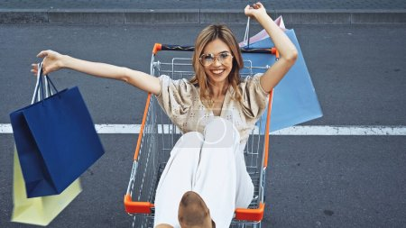 cheerful woman holding shopping bags while sitting in cart