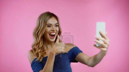 glückliche junge Frau zeigt Daumen nach oben, während Selfie isoliert auf rosa