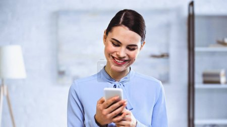happy businesswoman smiling while chatting on smartphone in office