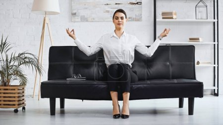 Photo for Successful businesswoman meditating while sitting on couch in office - Royalty Free Image