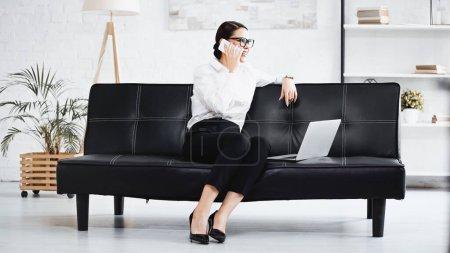 Photo pour Femme d'affaires souriante parlant sur un téléphone mobile près d'un ordinateur portable sur un canapé noir - image libre de droit