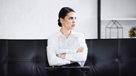Photo for Thoughtful businesswoman looking away while sitting on sofa with crossed arms - Royalty Free Image