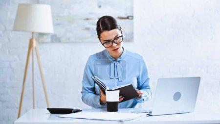 mujer de negocios concentrada buscando en portátil cerca de café para ir y portátil