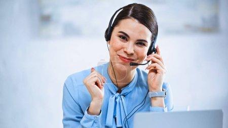 Photo pour Opérateur joyeux de centre d'appels souriant à la caméra tout en travaillant dans le bureau - image libre de droit