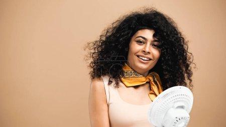 Photo pour Femme hispanique joyeuse debout près du ventilateur isolé sur beige - image libre de droit
