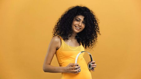 Pregnant hispanic woman holding headphones near belly isolated on yellow