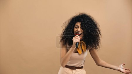 hispanic woman singing in microphone isolated on beige