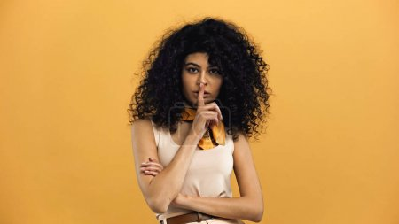 Photo pour Femme hispanique montrant geste secret à la caméra isolé sur jaune - image libre de droit