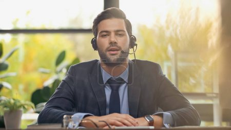 bearded operator in headset with microphone talking in office