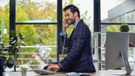 Photo pour Homme d'affaires joyeux parlant sur le téléphone rétro tout en s'appuyant sur la table - image libre de droit