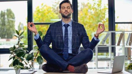Photo pour Homme d'affaires en costume méditant sur le bureau dans le bureau - image libre de droit