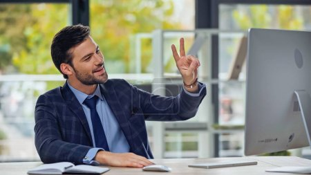 happy businessman showing peace sign while having video call in office