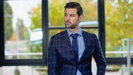 Photo for Businessman in suit with tie looking away in office - Royalty Free Image