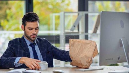 homme d'affaires regardant récipient en plastique avec salade