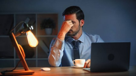 tired businessman touching eyes while working late in office