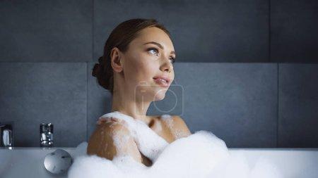 dreamy young woman taking bath with foam in white bathtub