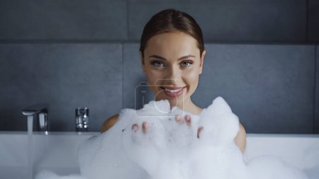 Photo for Smiling young woman taking bath with foam in white bathtub - Royalty Free Image