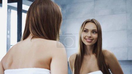 alegre joven mujer mirando el espejo y sonriendo en el baño