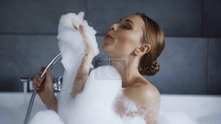 Photo pour Jeune femme prenant un bain dans la baignoire et soufflant de la mousse blanche - image libre de droit