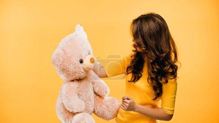 Photo pour Femme bouclée tenant ours en peluche rose isolé sur jaune - image libre de droit