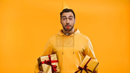 man blowing in party horn and holding presents isolated on yellow