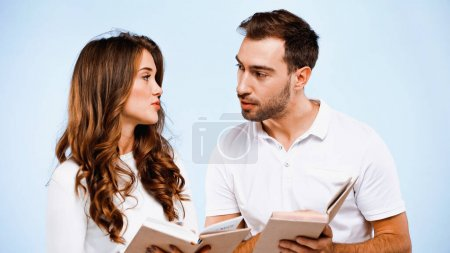 man and woman looking at each other and holding books isolated on blue