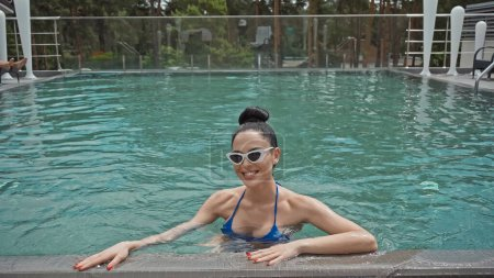happy young woman in sunglasses swimming in outdoor pool