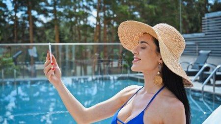 Photo pour Heureuse femme brune en chapeau de paille prendre selfie près de la piscine - image libre de droit