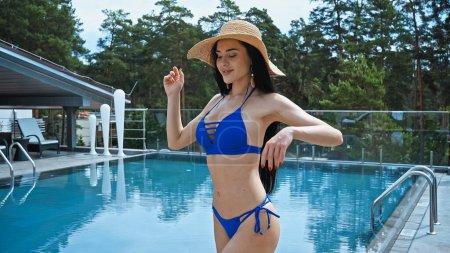 brunette woman in straw hat smiling near outdoor pool