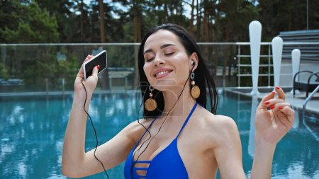 Frau mit Kopfhörer hört Musik und hält Smartphone in Poolnähe